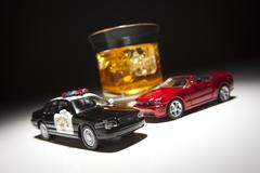 Stock Photo of Police and Sports Car Next to Alcoholic Drink Under Spot Light.