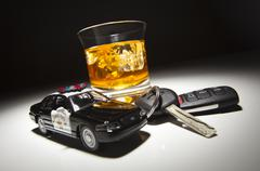 Highway Patrol Police Car Next to Alcoholic Drink and Keys Under Spot Light. - stock photo