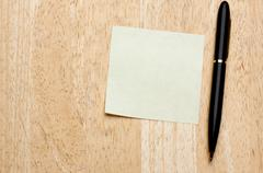 Pen and Post It Notes Pad Against a Wood Background - stock photo