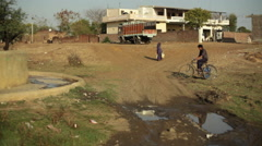 Village boy riding bicycle to get water at well, India, long shot Stock Footage
