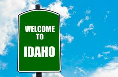 Green road sign with greeting message Welcome to IDAHO  Stock Photos