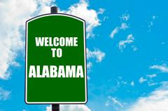 Green road sign with greeting message Welcome to ALABAMA  - stock photo