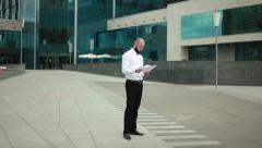 Businessman throwing paper near office building - stock footage
