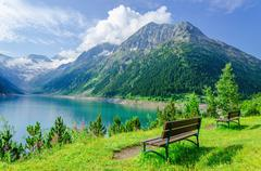 Empty bench and mountain lake, Zillertal, Austria Stock Photos