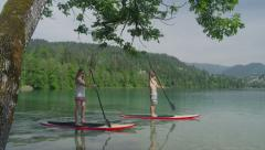 SLOW MOTION CLOSE UP: Young surfer couple SUPing along the lake land (part2) Stock Footage