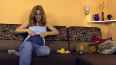 pregnant woman sit on couch and regulate special trousers strap - stock footage