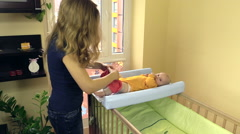 Mother dressing baby with pink pants. Kid lie on changing table Stock Footage