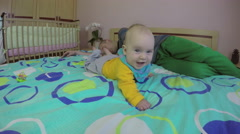 Sleeping father and playful baby on bed. Parental worry and joy. 4K Stock Footage