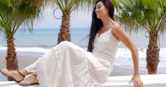 Woman in White Dress Sitting on Beach Wall Stock Footage