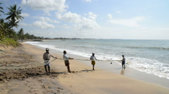 Local fishermen pull net from the ocean on the beach Stock Footage