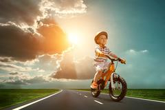 Child seating on the orange bicycle and travelling on the non-urban road unde Stock Photos
