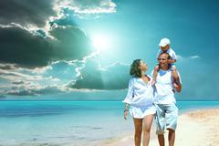 View of happy young family having fun on the beach Stock Photos