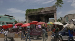 Stalls with red umbrellas in a street market in Haiti - stock footage