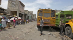 Driving cars and motorcycles in a food market in Haiti - stock footage