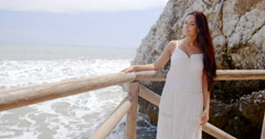 Young Lady in White Standing at Beach Railings - stock footage