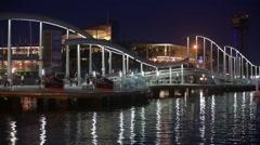 Stock Video Footage of Night view of Rambla de Mar, footbridge modern design in the port of Barcelona.
