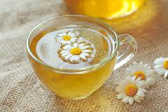 Chamomile tea herbal alternative medicine beverage in transparent cup with Stock Photos