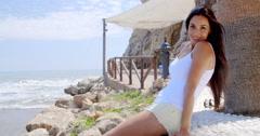 Brunette Woman Sitting on Stone Wall by Ocean Stock Footage