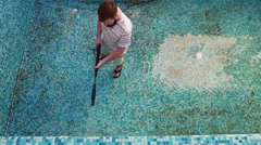A man is cleaning the pool wall - stock footage