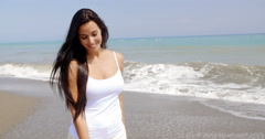 Brunette Woman Walking on Beach with Hand in Hair Stock Footage