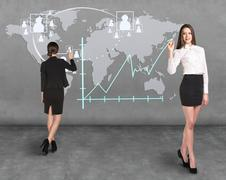 Businessladies in front of the map Stock Photos