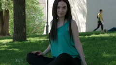 Casual brunette girl in green shirt sit on the grass crossed legs Stock Footage