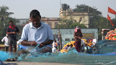 Fisherman repairs nets in a harbor in Mumbai Stock Footage