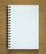 Blank spiral notepad on wood background Stock Photos