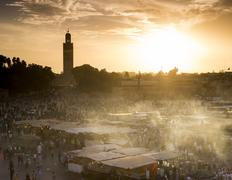 Djemaa el Fna square (Jemaa el Fna), Koutoubia Mosque in distance at sunset, - stock photo