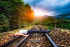 Girl lying on train tracks - stock photo