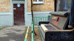 Threadbare pianoforte abandoned outdoors near the street - stock photo