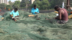 Three fishermen repair nets in the Sassoon Docks in Mumbai, India Stock Footage
