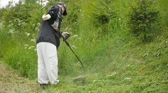 Man mowing down the green  grass  with fuel trimmer slow motion Stock Footage