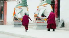 Tibetan Buddhist monks approach the Labrang Tibetan Buddhist Monastery Stock Footage