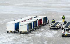 Service workers and baggage transport vehicles - stock photo