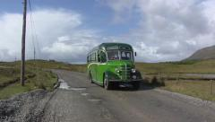 Old timer bus, coach on camera + pan Irish landscape at Connemara national park Stock Footage