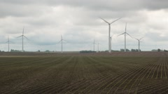 Furrows on Agriculture Farm in Foreground of Wind Turbines - stock footage