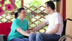 Nurse talking with young man in wheelchair - stock footage