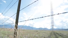 Barbwire in Foreground of High Voltage Power Lines - stock footage