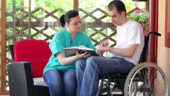 Physical therapist explaining exercises to young man in wheelchair - stock footage