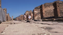 Two young tourists visiting the archaeological site of Pompeii Stock Footage