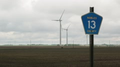 Wind Turbine Spinning Behind County Road Sign Stock Footage