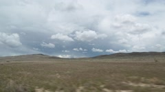 Passing Shot of Dry Western US Prairie with Hills and Clouds Stock Footage