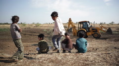 Children watching bulldozer develop area, India, long shot, shallow DOF - stock footage