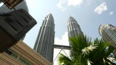 Petronas twin towers through palm leaves against blue sky, panning Stock Footage