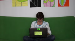 Woman Sitting On The Green Couch And Working On Laptop.Home Working Concept Stock Footage