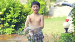 Happy asian child play splashing with rubber tube water on hot summer Stock Footage