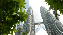 Beautiful dolly shot of iconic Petronas Twin Towers, sunny day, tree leafage Stock Footage