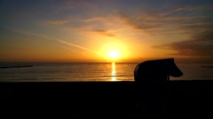 Silhouette from a beach chair at sunrise Stock Footage