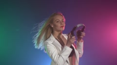 Beautiful, charming, dj girl in white jacket, putting headphones on her ears Stock Footage